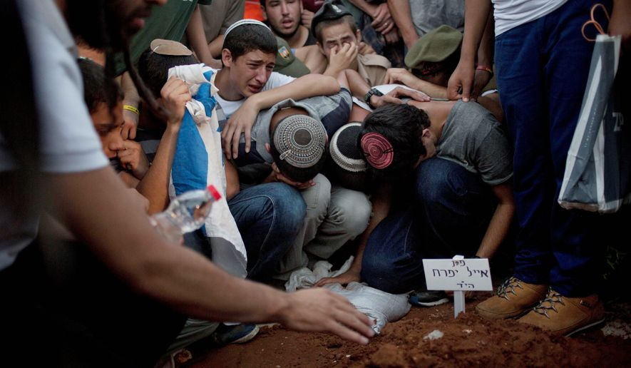 mourners: Family and friends of three Israeli teenagers who were abducted over two weeks ago mourn during their funeral in Modiin, Israel. Israeli leaders believe Hamas may be behind the taking and killing of the young men. (Associated Press)