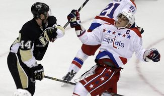 Pittsburgh Penguins defenseman Brooks Orpik (44) shoves Washington Capitals left wing Alex Ovechkin (8) from in front of the goal crease during a third-period power play in an NHL hockey game in Pittsburgh on Tuesday, March 19, 2013. The Penguins won 2-1.  (AP Photo/Gene J. Puskar)