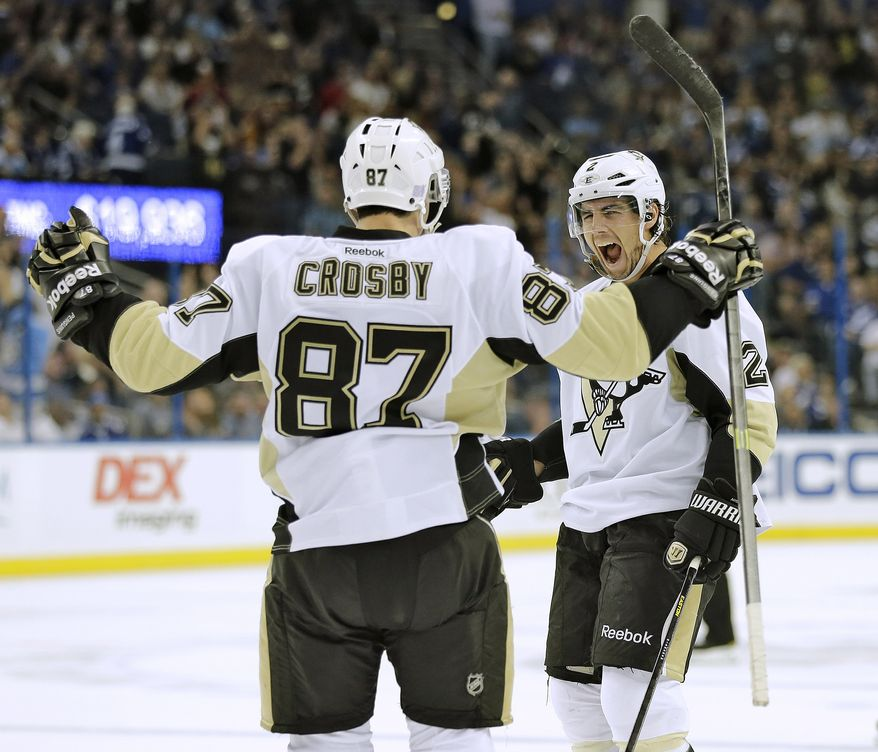 Pittsburgh Penguins defenseman Matt Niskanen (2) celebrates with teammate Sidney Crosby (87) after scoring against the Tampa Bay Lightning during the third period of an NHL hockey game Saturday, Oct. 12, 2013, in Tampa, Fla. The Penguins won the game 5-4. (AP Photo/Chris O'Meara)