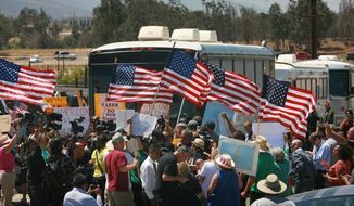 Protesters turn back three buses carrying 140 immigrants as they attempt to enter the Murrieta U.S. Border Patrol station for processing on Tuesday, July 1, 2014, in Murrieta, Calif.(AP Photo/The Press-Enterprise, David Bauman)  MAGS OUT; MANDATORY CREDIT