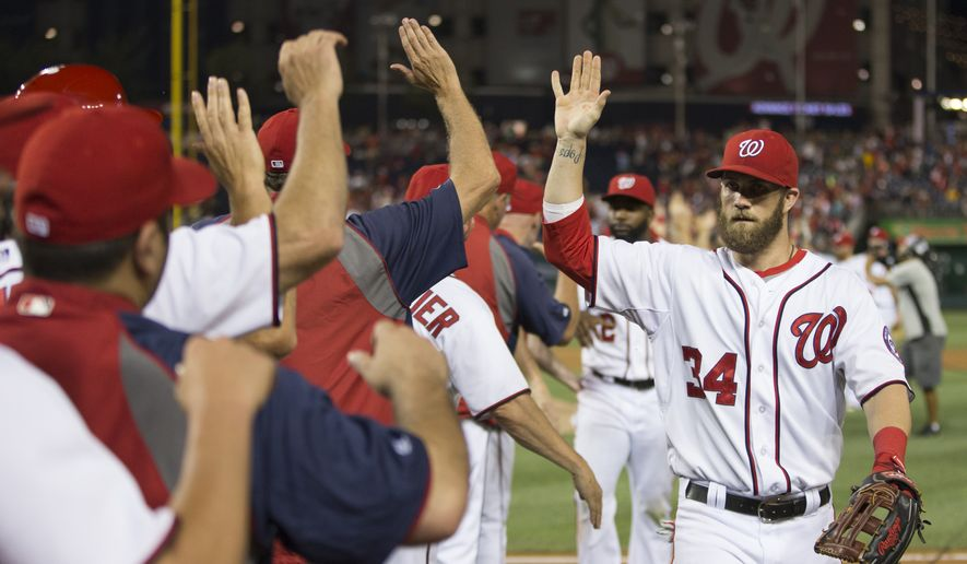Washington Nationals Bryce Harper is congratulated by teammates after a 7-3 victory over the Colorado Rockies at Nationals Park, on Monday, June 30, 2014, in Washington.  (AP Photo/ Evan Vucci)