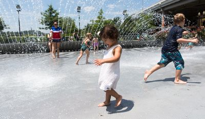 Two year old Metzli Rivas, from Norwalk, CA, walks through the fountain at Georgetown Waterfront Park Tuesday, as family friend Roxy Howard watches in the background. Keith Lane/Special to the Washington Times