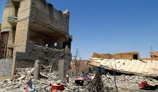 This photo taken on Tuesday, July 1, 2014, shows damaged homes due to clashes between fighters of the al-Qaida-inspired Islamic State of Iraq and the Levant (ISIL) and Iraqi security forces in Tikrit, 80 miles (130 kilometers) north of Baghdad, Iraq. The Islamic State of Iraq and the Levant announced this week that it has unilaterally established a caliphate in the areas under its control. It declared the group's leader, Abu Bakr al-Baghdadi, the head of its new self-styled state governed by Shariah law and demanded that all Muslims pledge allegiance to him. (AP Photo)