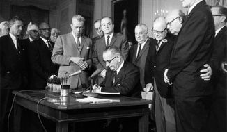President Lyndon Johnson signing the 1964 Civil Rights Act at the White House with key Senate allies Everett Dirksen (R-Ill.), standing at left, and Hubert Humphrey (D-Minn.), standing behind Johnson. (AP Photo, File)