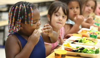 Nearly 48 million U.S. children lived in homes enrolled in at least one government program in 2011. This included about 35 million children who participated in the National School Lunch Program. (AP Photo/Sioux City Journal, Jim Lee)