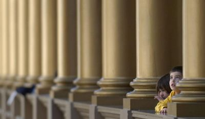Eli Marshall, right, 5, and his sister Abby, 4, watch model airplanes soar while standing between Corinthian columns on the second floor of the National Building Museum. (the washington times)