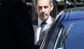 Former French President Nicolas Sarkozy leaves his house in Paris, Wednesday, July 2, 2014. Sarkozy, his lawyer and a magistrate are facing preliminary charges in a corruption investigation linked to allegations that he took 50 million euros ($67 million) in illegal campaign funds from Libya's Moammar Gadhafi, after a night of questioning by judicial officials. (AP Photo/Jacques Brinon)