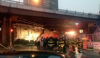 This photo provided by Roberto Danino shows emergency personal near a section of the facade inside an underpass of the Brooklyn Bridge after it had collapsed, Wednesday, July 2, 2014, in the Brooklyn borough of  New York. A fire department spokesman says five people were injured. (AP Photo/Roberto Danino)