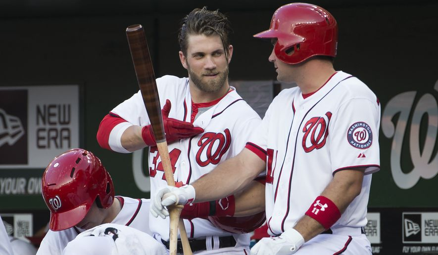 Washington Nationals Bryce Harper, left, talks with teammate Ryan Zimmerman during the first inning of a baseball game at Nationals Park, on Tuesday, July 1, 2014, in Washington. (AP Photo/ Evan Vucci)