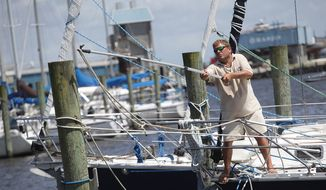 Oriental Harbor Marina dock master Mark Crowden stretches to loop an extra dock line around a post Wednesday afternoon, July 2, 2014, in Oriental, N.C. Although it's the boat owner's responsibility, he will walk the marina making sure the boats are safe and have enough dock lines to keep the boat and dock from crashing into each other during large waves expected from Tropical Storm Arthur as it brushes by Oriental. (AP Photo/Sun Journal, Chuck Beckley)