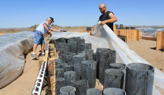 In this photo taken on Wednesday, July 2, 2014, a crew with Western Enterprises Inc. covers a row of fireworks shells that have been loaded into launching tubes at Balloon Fiesta Park in Albuquerque, N.M., for the city's annual Fourth of July festival. Officials in New Mexico and other drought-stricken states in the West have been urging residents to attend public fireworks displays rather than lighting their own fireworks due to dry conditions and high fire danger. (AP Photo/Susan Montoya Bryan)