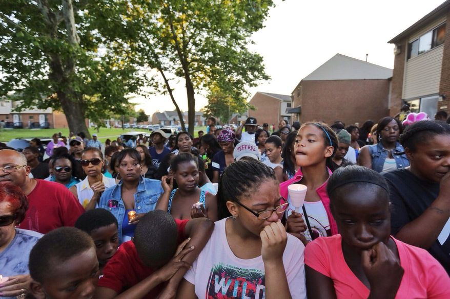 Shaybrielle Phillips, center, and D'Maia Pearce, right, both of Inkster, Mich., shed tears while standing with a large group gathered for a memorial outside the Parkside Estates housing complex in Inkster on Thursday, July 3, 2014, A 24-year-old man has been charged with first-degree murder in the death of a 2-year-old Detroit-area girl who was shot in a possible case of retaliation at the complex. (AP Photo/Detroit Free Press, Ryan Garza)