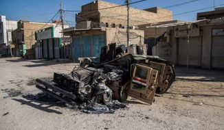 A burned Iraqi army vehicle on a street after clashes between followers of Shiite cleric Mahmoud al-Sarkhi and ISIL in Karbala. (Associated Press)