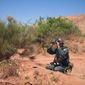 **FILE** An Algerian gendarme watches through his binoculars as he patrols in the desert near Bechar at the Moroccan border, about 1,000 km west of Algiers, on May 24, 2009. (Associated Press)
