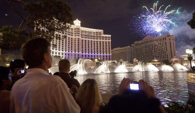 Tourists watch Independence Day weekend fireworks explode over Caesar's Palace as the Bellagio fountain show plays simultaneously, in Las Vegas. (AP Photo/Julie Jacobson)