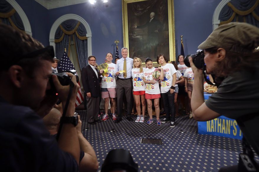 New York City Mayor Bill de Blasio poses for photos with contestants for the upcoming Nathan's Famous Fourth of July Hot-Dog Eating Contest tomorrow Thursday, July 3, 2014, at City Hall in New York. (AP Photo/Frank Franklin II)