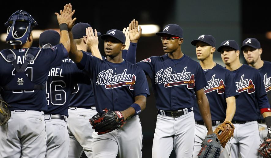Atlanta Braves' Justin Upton, center left, and his brother B.J. Upton, center right, celebrate with teammates after the Braves defeated the Houston Astros 3-2 in a baseball game Tuesday, June 24, 2014, in Houston. (AP Photo/David J. Phillip)