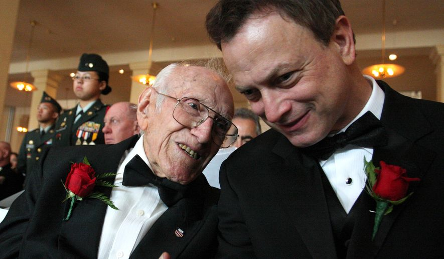 "In this May 10, 2008, file photo provided by the National Ethnic Coalition, 91-year-old World War II veteran and member of the U.S. Olympic team during the 1936 Berlin Olympics Louis Zamperini, left, shares a moment with actor and founder of ""Operation Iraqi Children"" Gary Sinise before the start of the 2008 Ellis Island Medals of Honor ceremony on Ellis Island. (AP Photo/National Ethnic Coalition, Tina Fineberg, File)"