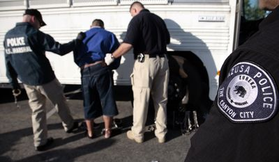 Authorities restrain a suspect in connection with a 2011 federal indictment accusing Latino street gang Azusa 13 of conspiring to drive blacks out of Azusa, Ca. through terror and violence. (AP Photo/Jason Redmond)