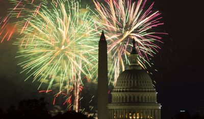 Fireworks illuminate the sky over the U.S. Capitol building and the Washington Monument during Fourth of July celebrations, on Friday, July 4, 2014, in Washington. (AP Photo/Evan Vucci)