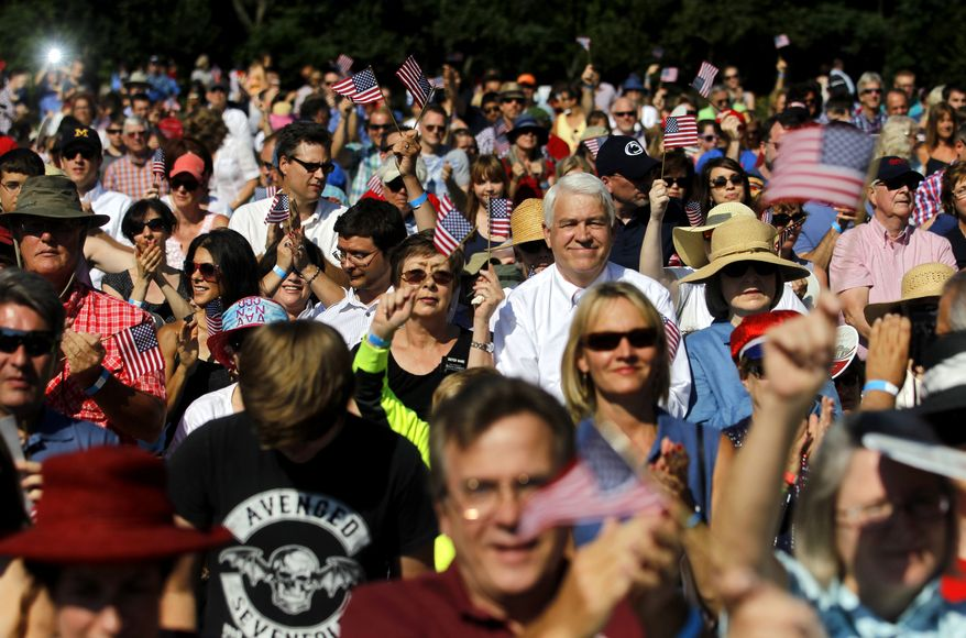 Spectators cheer and wave American flags after the naturalization of new U.S. citizens during the annual Independence Day celebration and naturalization ceremony at Monticello in Charlottesville, Va. on Friday, July 4, 2014. (AP Photo/The Daily Progress, Ryan M. Kelly)