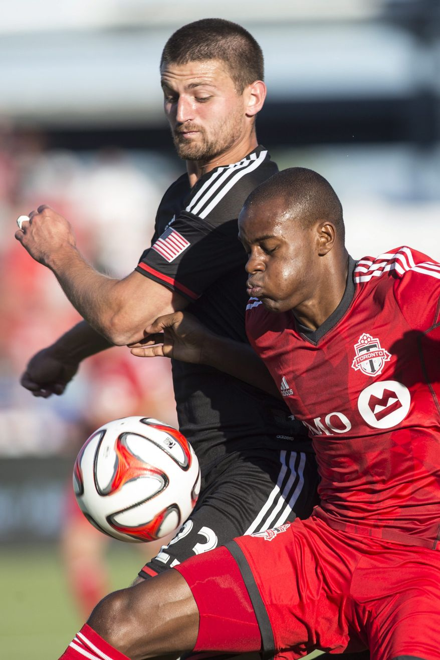 Toronto FC 's Jackson Goncalves, right, battles for the ball with D.C. United's Perry Kitchen during first-half MLS soccer game action in Toronto, Saturday, July 5, 2014. (AP Photo/The Canadian Press, Chris Young)