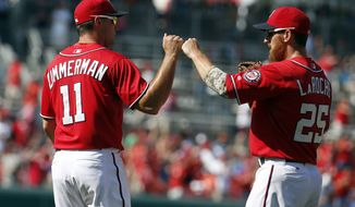 Washington Nationals' Ryan Zimmerman (11) celebrates with Adam LaRoche (25) after a baseball game against the Chicago Cubs at Nationals Park, Sunday, July 6, 2014, in Washington. The Nationals won 2-1. (AP Photo/Alex Brandon)