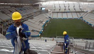 Workers clean the stairs at Arena Corinthians in Sao Paulo. Brazil faces a shortage of up to 8.5 million workers in 2020 if it hopes to maintain current growth rates, according to a report from the Boston Consulting Group. The United States is forecast to have a surplus of up to 22 million workers in 2020. (Associated Press)