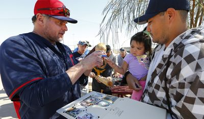Cleveland Indians' Jason Giambi signs autographs for fans during spring training baseball practice in Goodyear, Ariz., Monday, Feb. 17, 2014. (AP Photo/Paul Sancya)