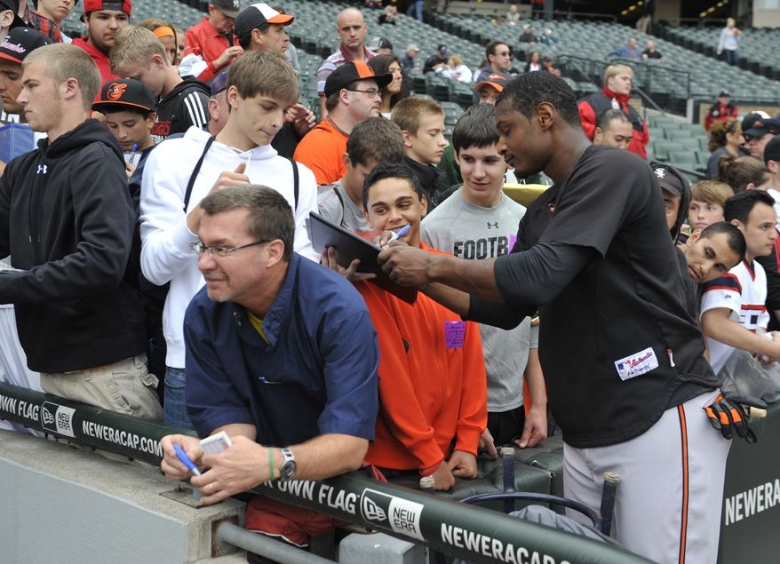 Baltimore Orioles' Adam Jones signs autographs before a baseball game against the Chicago White Sox Tuesday, July 2, 2013 in Chicago.  (AP Photo/David Banks)