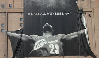 """FILE - In this July 11, 2010 file photo, A 10-story banner of former Cleveland Cavaliers NBA basketball star LeBron James is taken down by workers in downtown Cleveland, Ohio. As Cavaliers fans breathlessly await a homecoming they never thought possible, the broken relationship between James and Dan Gilbert could get in the way. When James left Cleveland four years ago as a free agent to chase NBA championship in Miami, Gilbert publicly attacked him, calling the superstar's departure """"cowardly"""" and accusing him of quitting in playoff games.(AP Photo/Amy Sancetta, File)"""