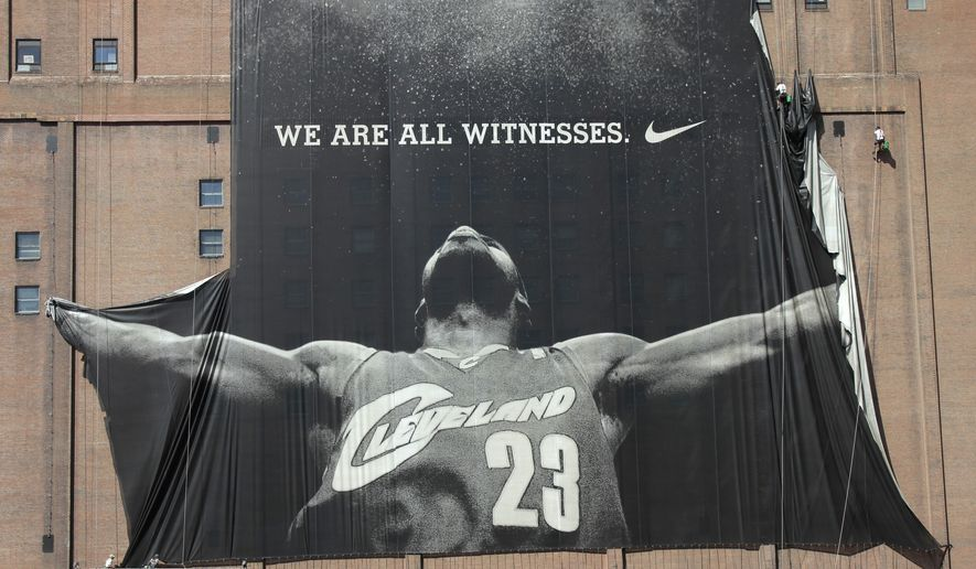 "FILE - In this July 11, 2010 file photo, A 10-story banner of former Cleveland Cavaliers NBA basketball star LeBron James is taken down by workers in downtown Cleveland, Ohio. As Cavaliers fans breathlessly await a homecoming they never thought possible, the broken relationship between James and Dan Gilbert could get in the way. When James left Cleveland four years ago as a free agent to chase NBA championship in Miami, Gilbert publicly attacked him, calling the superstar's departure ""cowardly"" and accusing him of quitting in playoff games.(AP Photo/Amy Sancetta, File)"