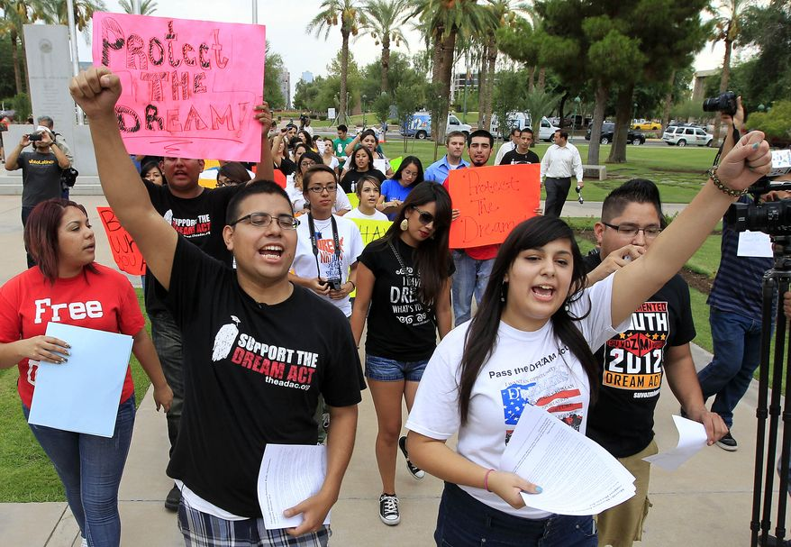 **FILE** Joshua Montano (left) and Deborah Robles protest in front of the Arizona Capitol in Phoenix on Aug. 16, 2012, the day after Gov. Jan Brewer, in an executive order, reaffirmed Arizona state law denying young illegal immigrants driver's licenses and other public benefits in Phoenix. (Associated Press)