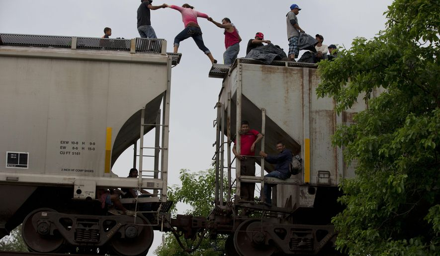 A woman is helped from one boxcar to another, as Central American migrants wait atop the train they were riding north, hours after it suffered a minor derailment in a remote wooded area outside Reforma de Pineda, Chiapas state, Mexico, on June 20, 2014. Many migrants who say they are fleeing criminal violence generally are not eligible for political asylum, which is reserved for groups persecuted for their beliefs or identities. U.N. officials say there is no way of forcing the U.S. and Mexico to accept Central Americans as refugees, but a broad-based change in terminology could bring pressure on the two countries to do more. (Associated Press) **FILE**