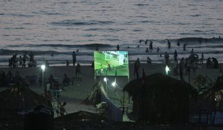FILE - In this Thirsday, June 19, 2014 file photo, Palestinians watch a World Cup football game on a wide screen on the beach of Gaza City. Politics and conflict are never far from soccer in the Middle East, but this year's World Cup has been entangled with unprecedented sectarian violence and soaring tensions between Arab countries, pushing fans to watch matches in secret or even on a channel owned by region's number one enemy _ Israel.(AP Photo/Khalil Hamra, File)