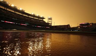 The orange sky is reflected in a puddle during a rain delayed start of an interleague baseball game between the Washington Nationals and the Baltimore Orioles at Nationals Park, Tuesday, July 8, 2014, in Washington. (AP Photo/Alex Brandon)