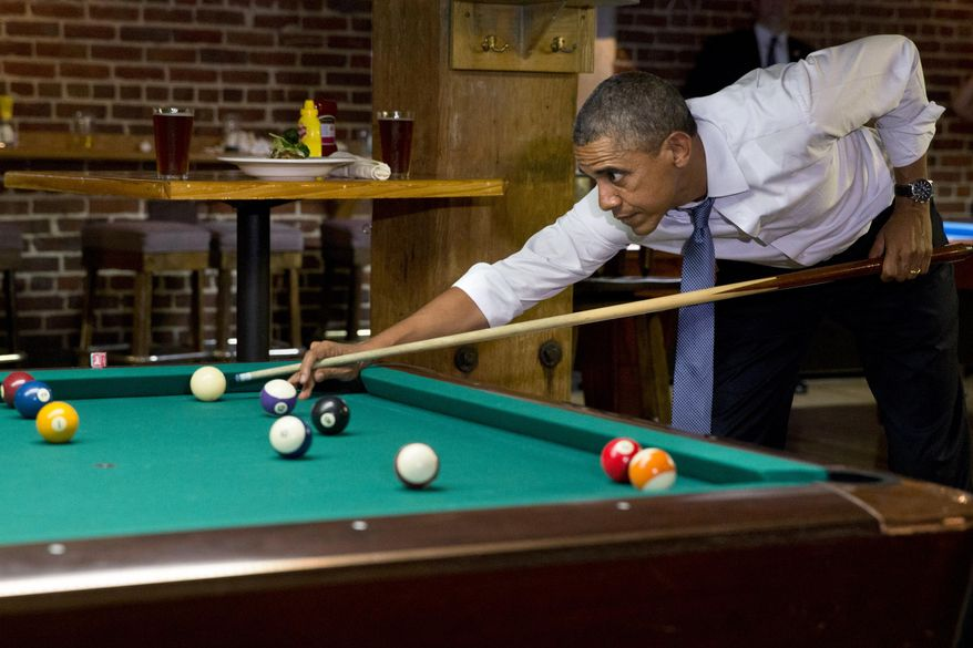 President Barack Obama plays pool at Wynkoop Brewing Co. with Colorado Gov. John Hickenlooper, not seen, Tuesday, July 8, 2014, in Denver. (AP Photo/Jacquelyn Martin)
