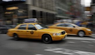 FILE - In this Thursday, Feb. 27, 2014 file photo, New York City taxis drive through New York's Times Square. The car-hailing service Uber is taking on New York City's taxis, temporarily dropping some of its prices by 20 percent starting Monday, July 7, 2014. (AP Photo/Richard Drew)
