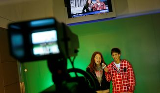 "Sarah Cohen, left, and Keaton Renta, both of La Verne, Ca., try out the ""Be A TV Reporter"" exhibit during a preview of the Newseum in Washington, Tuesday, April 8, 2008. The Newseum, a museum about the news, is scheduled to open Friday April 11, 2008. (AP Photo/Jacquelyn Martin)"