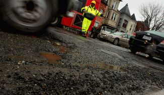"A worker directs traffic through potholes along Florida Avenue in Northwest. The D.C. Department of Transportation classifies 38 percent of locally funded roadways as being in ""poor,"" ""very poor,"" or ""failed"" condition. (Andrew Harnik/The Washington Times)"