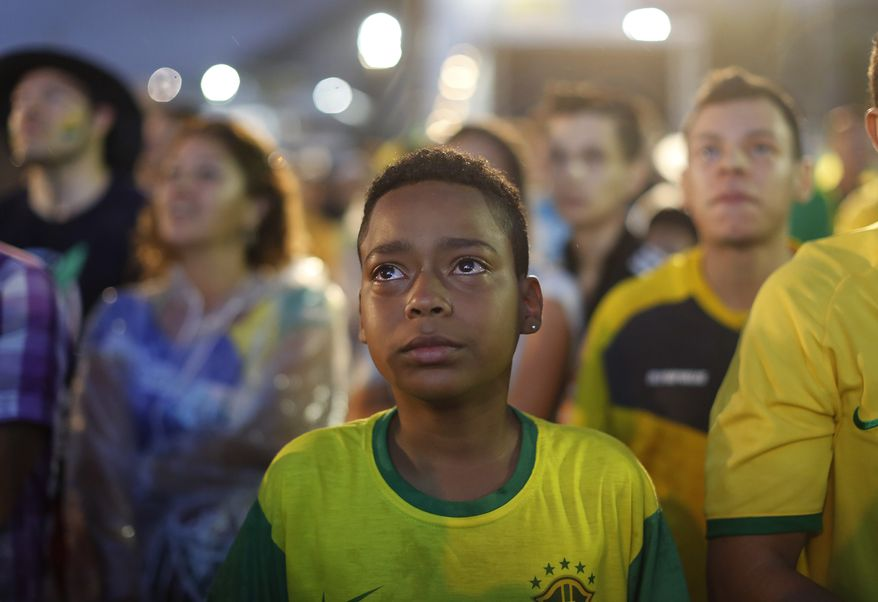 A Brazil soccer fan cries as he watches his team get beat during a live telecast of the semi-finals World Cup soccer match between Brazil and Germany, inside the FIFA Fan Fest area on Copacabana beach in Rio de Janeiro, Brazil, Tuesday, July 08, 2014. (AP Photo/Leo Correa)