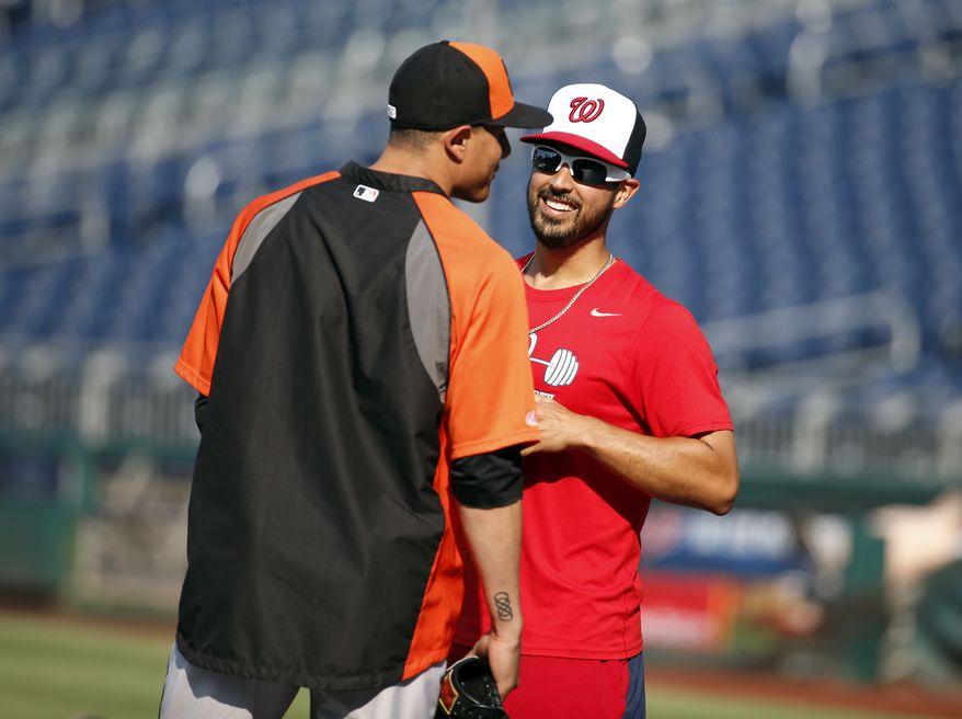 Baltimore Orioles third baseman Manny Machado, left, talks with Washington Nationals starting pitcher Gio Gonzalez before an interleague baseball game at Nationals Park, Monday, July 7, 2014, in Washington. (AP Photo/Alex Brandon)