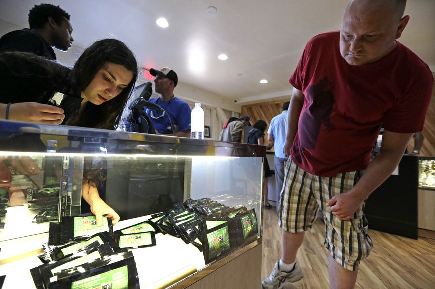 Clerk Havilah Nokes arranges packets of marijuana for sale as a customer peers in at the display at Cannabis City on the first day of legal recreational pot sales Tuesday, July 8, 2014, in Seattle. Washington on Tuesday became the second state to allow people to buy marijuana legally in the U.S. without a doctor's note as eager customers who lined up outside stores made their purchases. (AP Photo/Elaine Thompson)