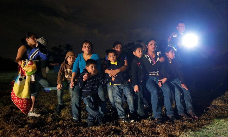 ** FILE ** A group of immigrants from Honduras and El Salvador are stopped at the U.S.-Mexico border in Granjeno, Texas. (Associated Press)
