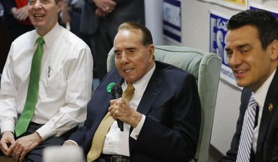 ** FILE ** Former Sen. Bob Dole, R-Kan., center, takes questions while seated between Gov. Sam Brownback, left, and Rep. Kevin Yoder, R-Kan., right, during a visit to the Johnson County Republican Headquarters in Overland Park, Kan., Monday, April 21, 2014. (AP Photo/Orlin Wagner)