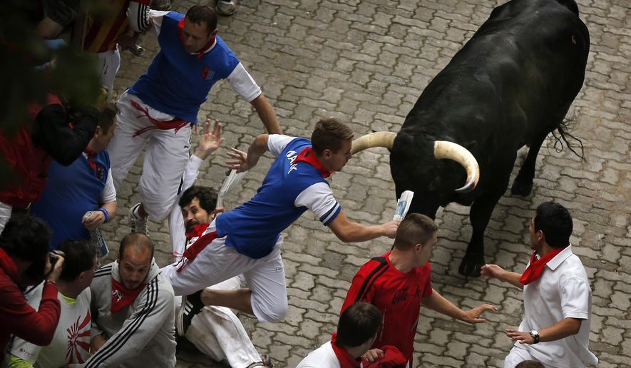 U.S. runner Bill Hillmann, 35, from Chicago, center left, falls seconds before a Victoriano del Rio ranch fighting bull gored him on his right leg during the running of the bulls of the San Fermin festival, in Pamplona, Spain, Wednesday, July 9, 2014. (AP Photo/Daniel Ochoa de Olza) ** FILE **