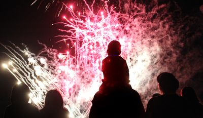 **FILE** Angel Chavez, 3, watches a fireworks show from the shoulders of his father, Jose Chavez, in Bartlett, Tenn., on July 3, 2014. (Associated Press/The Commercial Appeal)
