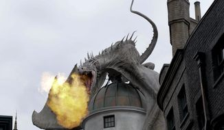 This June 19, 2014 file photo shows a dragon breathing fire from atop Gringnotts Bank during a preview of Diagon Alley at the Wizarding World of Harry Potter at Universal Orlando, in Orlando, Fla. For a second day in a row, visitors waited up to five hours to get on the ride, Harry Potter and the Escape from Gringotts, located in the new Diagon Alley section of Universal Studios. On Tuesday, July 8, on the first day Diagon Alley was open to the public, visitors waited for as long as seven hours. (AP Photo/John Raoux, File)