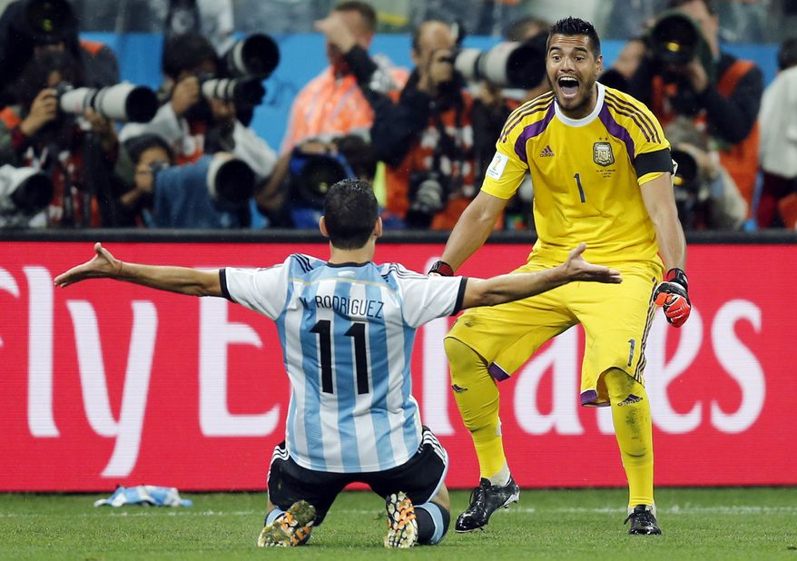Argentina's Maxi Rodriguez, left, celebrates with goalkeeper Sergio Romero after scoring the decisive goal during the World Cup semifinal soccer match between the Netherlands and Argentina at the Itaquerao Stadium in Sao Paulo, Brazil, Wednesday, July 9, 2014. Argentina beat the Netherlands 4-2 in a penalty shootout to reach the World Cup final. (AP Photo/Frank Augstein)