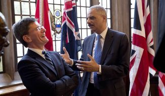 The U.S. Attorney General Eric Holder, right, jokes with New Zealand's Attorney General Chris Finlayson QC, as they chat after posing for a group photograph before an evening dinner in the Grand Hall of Gray's Inn in London, Wednesday, July 9, 2014.  The Attorneys General from Australia, Britain, Canada, New Zealand and the U.S. are meeting in London for a conference July 9 to 11 to discuss emerging issues and existing trends in fighting international cybercrime.  (AP Photo/Matt Dunham)